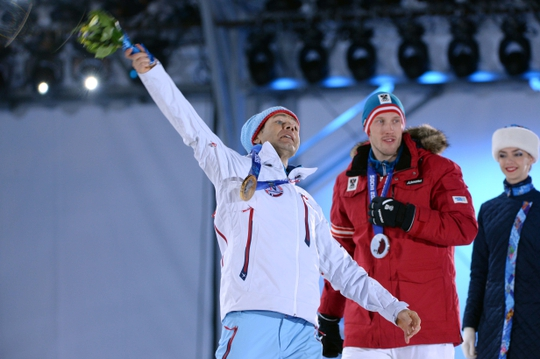 Feb 9, 2014; Sochi, RUSSIA; Ole Einar Bjoerndalen (NOR) throws his bouquet of flowers into the crowd in the medal ceremony for the men's 10km biathlon sprint during the Sochi 2014 Olympic Winter Games at Medals Plaza. Mandatory Credit: Kyle Terada-USA TODAY Sports