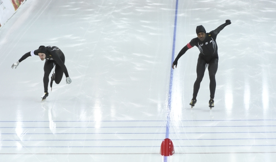 Feb 10, 2014; Sochi, RUSSIA; American Shani Davis, right, edges out teammate Mitchell Whitmore during the men's speed skating 500m race two during the Sochi 2014 Olympic Winter Games at Adler Arena Skating Center. Mandatory Credit: Robert Hanashiro-USA TODAY Sports