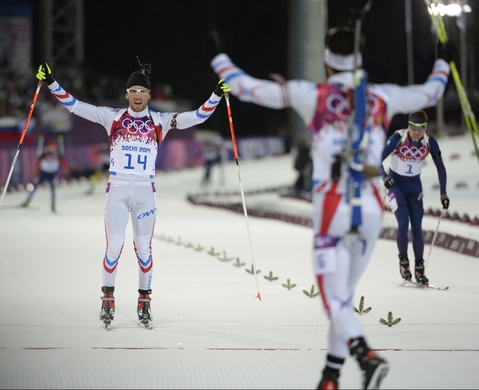 Feb 10, 2014; Krasnaya Polyana, RUSSIA; Gold medalist Martin Fourcade (FRA) greets his countryman Jean Guillaume Beatrix (FRA) as he crosses the line to win the bronze medal during the Sochi 2014 Olympic Winter Games at Laura Cross-Country Ski and Biathlon Center. Ole Einar Bjoerndalen (NOR) at right, finished in fourth. Mandatory Credit: Jack Gruber-USA TODAY Sports