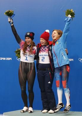 Feb 14, 2014; Krasnaya Polyana, RUSSIA; Elizabeth Yarnold (GBR) (center), Noelle Pikus-Pace (USA) (left) and Elena Nikitina (RUS) celebrate on the podium following the ladies skeleton during the Sochi 2014 Olympic Winter Games at Sanki Sliding Center. Mandatory Credit: Kevin Jairaj-USA TODAY Sports