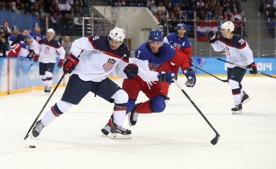 Feb 19, 2014; Sochi, RUSSIA; USA forward Zach Parise (9) controls the puck against Czech Republic defenseman Tomas Kaberle (7) in the men's ice hockey quarterfinals during the Sochi 2014 Olympic Winter Games at Shayba Arena. Mandatory Credit: Winslow Townson-USA TODAY Sports