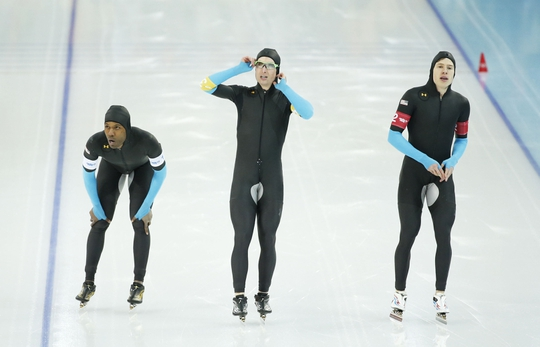 Feb 21, 2014; Sochi, RUSSIA; (Left to right) Shani Davis, Jonathan Kuck, and Brian Hansen, all of the USA, react after their heat in the Speed Skating men's team pursuit quarterfinals during the Sochi 2014 Olympic Winter Games at Adler Arena Skating Center. Mandatory Credit: Jeff Swinger-USA TODAY Sports