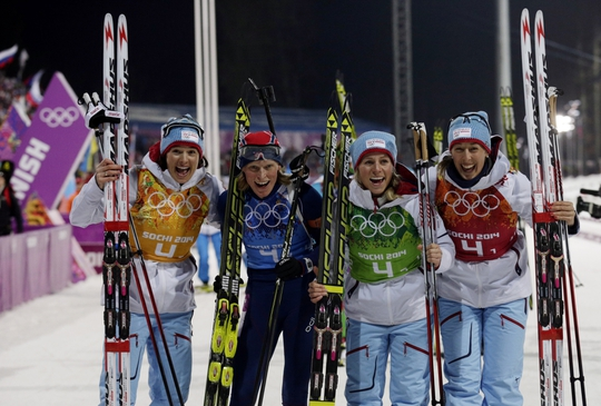 Feb 21, 2014; Krasnaya Polyana, RUSSIA; The Norway team (from left to right) Ann Kristin Aafedt Flatland (yellow) and Tora Berger (blue) and Tiril Eckhoff (green) and Fanny Welle-Strand Horn (red) celebrate after the women's 4x6km relay biathlon during the Sochi 2014 Olympic Winter Games at Laura Cross-Country Ski and Biathlon Center. Mandatory Credit: Andrew P. Scott-USA TODAY Sports