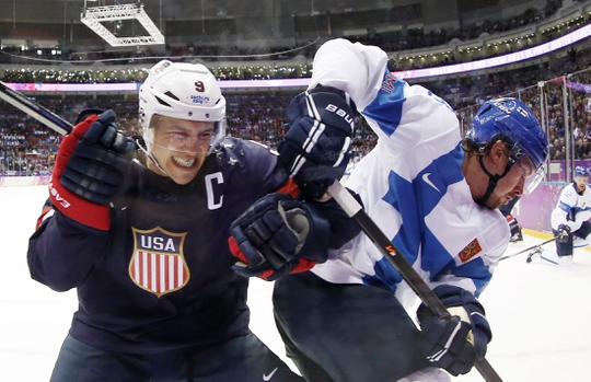 Feb 22, 2014; Sochi, RUSSIA; USA forward Zach Parise (9) battles for the puck along the boards with Finland defenseman Sami Lepisto (18) in the men's ice hockey bronze medal game during the Sochi 2014 Olympic Winter Games at Bolshoy Ice Dome. Mandatory Credit: Winslow Townson-USA TODAY Sports