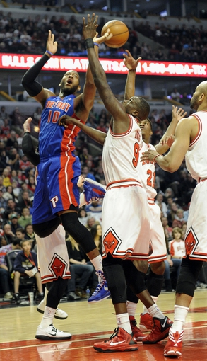 Mar 31, 2013; Chicago, IL, USA; Detroit Pistons center Greg Monroe (10) and Chicago Bulls small forward Luol Deng (9) reach for a rebound during the first half at the United Center. Mandatory Credit: David Banks-USA TODAY Sports