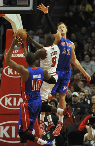 Mar 31, 2013; Chicago, IL, USA;  Detroit Pistons power forward Jonas Jerebko (33) defends Chicago Bulls small forward Luol Deng (9) during the first half at the United Center. Mandatory Credit: David Banks-USA TODAY Sports