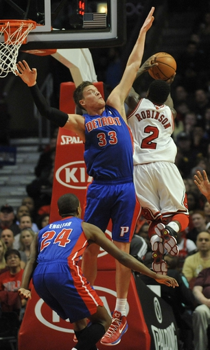 Mar 31, 2013; Chicago, IL, USA; Detroit Pistons power forward Jonas Jerebko (33) defends Chicago Bulls point guard Nate Robinson (2) during the first half at the United Center. Mandatory Credit: David Banks-USA TODAY Sports