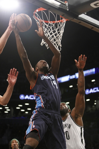 Apr 6, 2013; Brooklyn, NY, USA; Charlotte Bobcats forward Michael Kidd-Gilchrist (14) puts up a shot against Brooklyn Nets forward Reggie Evans (30) in the first quarter at Barclays Center. Mandatory Credit: Nicole Sweet-USA TODAY Sports