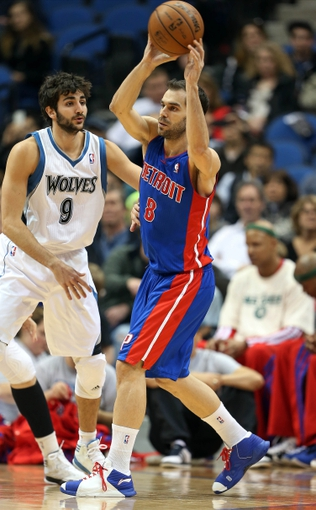 Apr 6, 2013; Minneapolis, MN, USA; Detroit Pistons point guard Jose Calderon (8) passes the ball around Minnesota Timberwolves point guard Ricky Rubio (9) in the first half at Target Center. Mandatory Credit: Jesse Johnson-USA TODAY Sports