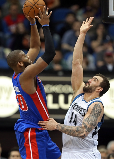 Apr 6, 2013; Minneapolis, MN, USA; Detroit Pistons center Greg Monroe (10) goes up for a shot over Minnesota Timberwolves center Nikola Pekovic (14) in the first half at Target Center. Mandatory Credit: Jesse Johnson-USA TODAY Sports