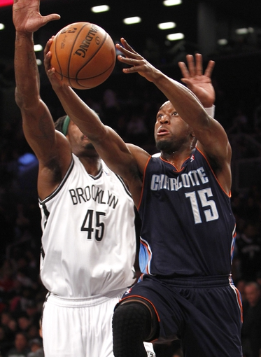 Apr 6, 2013; Brooklyn, NY, USA; Charlotte Bobcats guard Kemba Walker (15) puts up a shot against Brooklyn Nets forward Gerald Wallace (45) in the first quarter at Barclays Center. Mandatory Credit: Nicole Sweet-USA TODAY Sports
