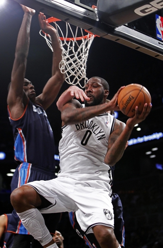 Apr 6, 2013; Brooklyn, NY, USA; Brooklyn Nets forward Andray Blatche (0) passes the ball against Charlotte Bobcats forward Bismack Biyombo (0) in the fourth quarter at Barclays Center. Nets won 105-96. Mandatory Credit: Nicole Sweet-USA TODAY Sports