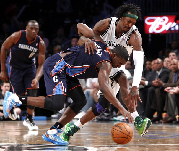 Apr 6, 2013; Brooklyn, NY, USA; Charlotte Bobcats guard Ben Gordon (8) fights for a loose ball against Brooklyn Nets forward Gerald Wallace (45) in the fourth quarter at Barclays Center. Nets won 105-96. Mandatory Credit: Nicole Sweet-USA TODAY Sports