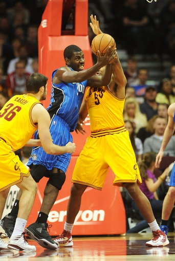 Apr 7, 2013; Cleveland, OH, USA; Orlando Magic power forward Andrew Nicholson (44) goes up for a shot against Cleveland Cavaliers power forward Kevin Jones (5) and small forward Omri Casspi (36) during the game at Quicken Loans Arena. Mandatory Credit: Eric P. Mull-USA TODAY Sports