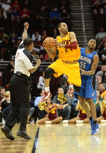 Apr 7, 2013; Cleveland, OH, USA; Cleveland Cavaliers shooting guard Wayne Ellington (21) is fouled by Orlando Magic shooting guard E'Twaun Moore (55) during the game at Quicken Loans Arena. Mandatory Credit: Eric P. Mull-USA TODAY Sports
