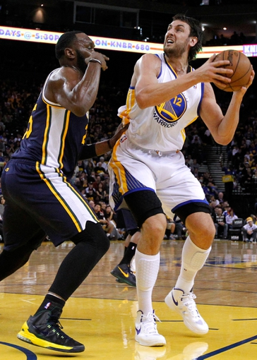 Apr 7, 2013; Oakland, CA, USA; Golden State Warriors center Andrew Bogut (12) looks to shoot the ball over Utah Jazz center Al Jefferson (25) in the first quarter at ORACLE arena. Mandatory Credit: Cary Edmondson-USA TODAY Sports