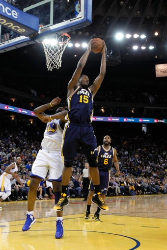 Apr 7, 2013; Oakland, CA, USA; Utah Jazz forward Derrick Favors (15) grabs a rebound over Golden State Warriors forward Carl Landry (7) in the second quarter at ORACLE arena. Mandatory Credit: Cary Edmondson-USA TODAY Sports