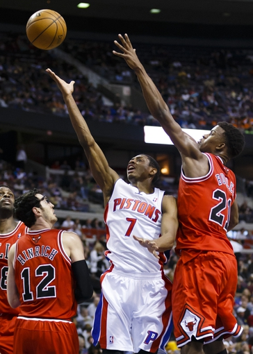 April 7, 2013; Auburn Hills, MI, USA; Detroit Pistons point guard Brandon Knight (7) goes to the basket on Chicago Bulls shooting guard Kirk Hinrich (12) and small forward Jimmy Butler (21) in the third quarter at The Palace. Detroit won 99-85. Mandatory Credit: Rick Osentoski-USA TODAY Sports