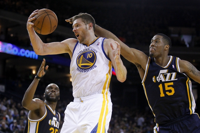 Apr 7, 2013; Oakland, CA, USA; Golden State Warriors forward David Lee (10) pulls down a rebound next to Utah Jazz forward Derrick Favors (15) in the third quarter at ORACLE arena. The Jazz defeated the Warriors 97-90. Mandatory Credit: Cary Edmondson-USA TODAY Sports
