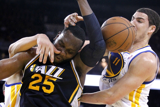 Apr 7, 2013; Oakland, CA, USA; Utah Jazz center Al Jefferson (25) is fouled while attempting a shot next to Golden State Warriors guard Klay Thompson (11) in the third quarter at ORACLE arena. The Jazz defeated the Warriors 97-90. Mandatory Credit: Cary Edmondson-USA TODAY Sports