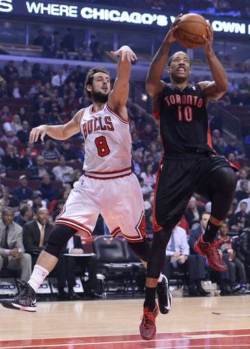 Apr 9, 2013; Chicago, IL, USA; Toronto Raptors shooting guard DeMar DeRozan (10) shoots the ball over Chicago Bulls shooting guard Marco Belinelli (8) during the first half at the United Center. Mandatory Credit: Mike DiNovo-USA TODAY Sports
