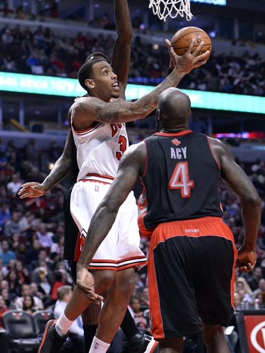 Apr 9, 2013; Chicago, IL, USA; Chicago Bulls power forward Malcolm Thomas (3) shoots the ball against Toronto Raptors small forward Quincy Acy (4) during the second half at the United Center. Toronto defeats Chicago 101-98. Mandatory Credit: Mike DiNovo-USA TODAY Sports