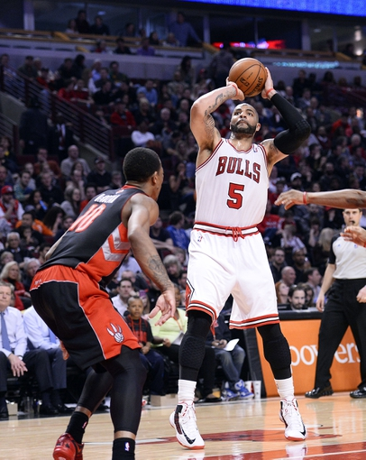 Apr 9, 2013; Chicago, IL, USA; Chicago Bulls power forward Carlos Boozer (5) shoots the ball over Toronto Raptors shooting guard DeMar DeRozan (10) during the second half at the United Center. Toronto defeats Chicago 101-98. Mandatory Credit: Mike DiNovo-USA TODAY Sports