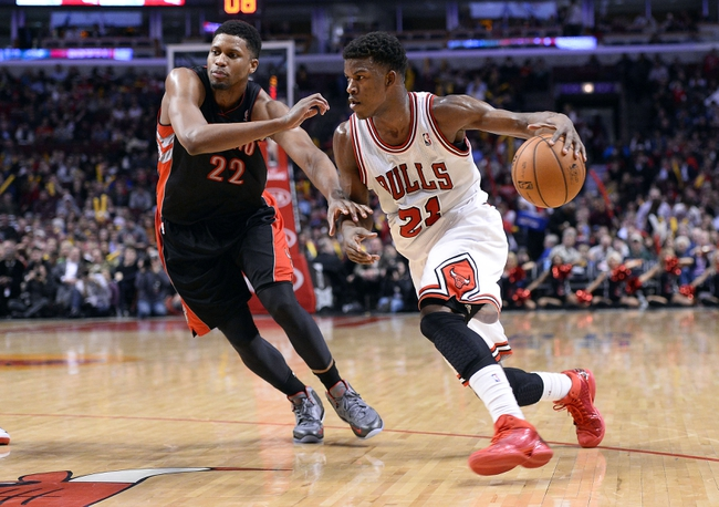 Apr 9, 2013; Chicago, IL, USA; Chicago Bulls small forward Jimmy Butler (21) dribbles the ball against Toronto Raptors small forward Rudy Gay (22) during the second half at the United Center. Toronto defeats Chicago 101-98. Mandatory Credit: Mike DiNovo-USA TODAY Sports
