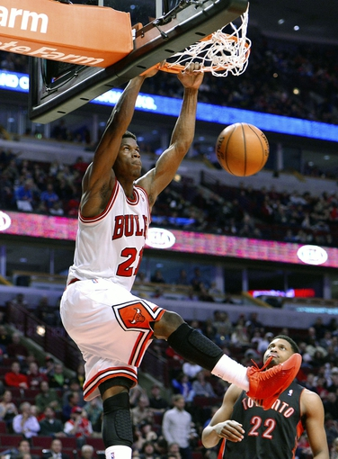 Apr 9, 2013; Chicago, IL, USA; Chicago Bulls small forward Jimmy Butler (21) dunks the ball against the Toronto Raptors during the second half at the United Center. Toronto defeats Chicago 101-98. Mandatory Credit: Mike DiNovo-USA TODAY Sports