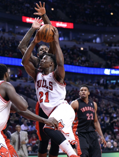 Apr 9, 2013; Chicago, IL, USA; Chicago Bulls small forward Jimmy Butler (21) shoots the ball over Toronto Raptors power forward Amir Johnson (15) during the second half at the United Center. Toronto defeats Chicago 101-98. Mandatory Credit: Mike DiNovo-USA TODAY Sports