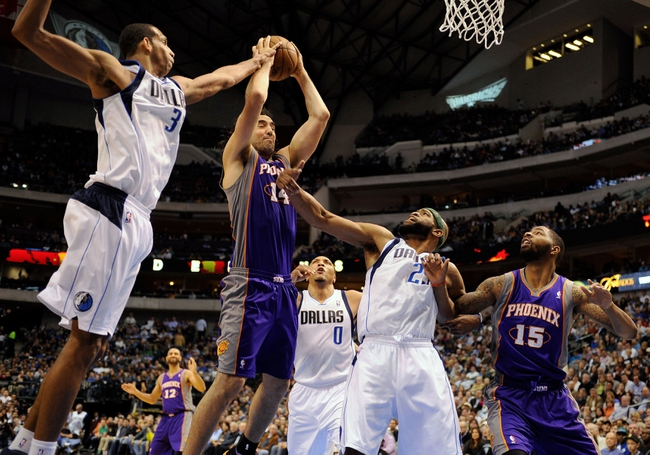 Apr 10, 2013; Dallas, TX, USA; Dallas Mavericks center Brandan Wright (34) and small forward Shawn Marion (0) and shooting guard Vince Carter (25) defend against Phoenix Suns power forward Luis Scola (14) during the second half at the American Airlines Center. The Suns defeated the Mavericks 102-91. Mandatory Credit: Jerome Miron-USA TODAY Sports