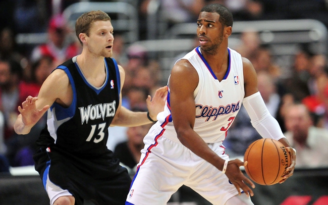 April 10, 2013; Los Angeles, CA, USA; Los Angeles Clippers point guard Chris Paul (3) controls the ball against the defense of Minnesota Timberwolves point guard Luke Ridnour (13) during the first half at Staples Center. Mandatory Credit: Gary A. Vasquez-USA TODAY Sports