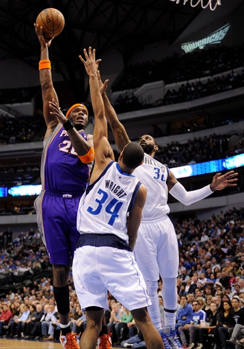 Apr 10, 2013; Dallas, TX, USA; Phoenix Suns center Jermaine O'Neal (20) shoots over Dallas Mavericks center Brandan Wright (34) and shooting guard O.J. Mayo (32) during the second half at the American Airlines Center. The Suns defeated the Mavericks 102-91. Mandatory Credit: Jerome Miron-USA TODAY Sports