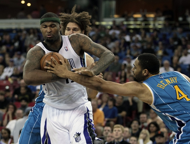 April 10, 2013; Sacramento, CA, USA; Sacramento Kings center DeMarcus Cousins (15) controls the rebound against New Orleans Hornets center Robin Lopez (15) and shooting guard Xavier Henry (4) during the fourth quarter at Sleep Train Arena. The Sacramento Kings defeated the New Orleans Hornets 121-110. Mandatory Credit: Kelley L Cox-USA TODAY Sports