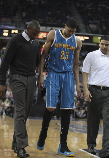 April 10, 2013; Sacramento, CA, USA; New Orleans Hornets power forward Anthony Davis (23) is assisted off the court to the locker room after spraining his left knee drawing an offensive foul by the Sacramento Kings during the fourth quarter at Sleep Train Arena. The Sacramento Kings defeated the New Orleans Hornets 121-110. Mandatory Credit: Kelley L Cox-USA TODAY Sports