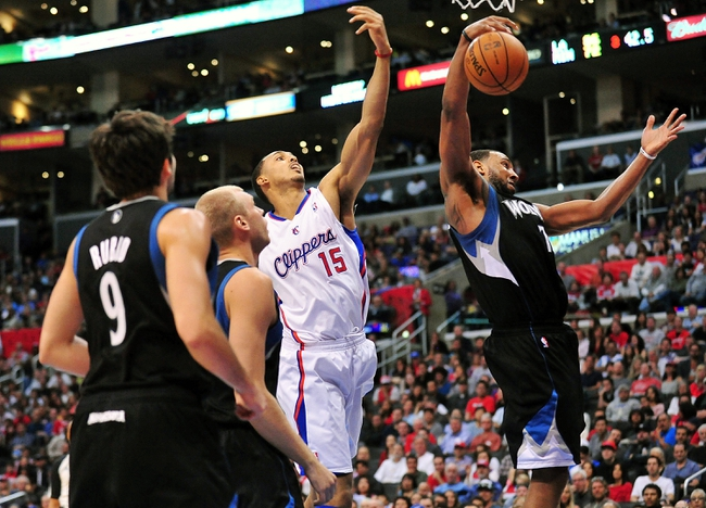 April 10, 2013; Los Angeles, CA, USA; Minnesota Timberwolves power forward Derrick Williams (7) grabs a rebound ahead of Los Angeles Clippers center Ryan Hollins (15) during the second half at Staples Center. Mandatory Credit: Gary A. Vasquez-USA TODAY Sports