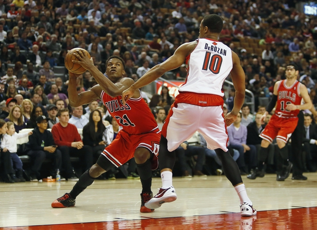 Apr 12, 2013; Toronto, Ontario, CAN; Chicago Bulls guard-forward Jimmy Butler (21) tries to get around Toronto Raptors guard DeMar DeRozan (10) at the Air Canada Centre. Mandatory Credit: John E. Sokolowski-USA TODAY Sports
