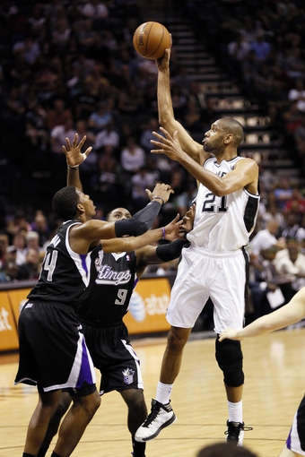 Apr 12, 2013; San Antonio, TX, USA; San Antonio Spurs forward Tim Duncan (21) takes a shot over Sacramento Kings forward Jason Thompson (34) and Patrick Patterson (9) during the first half at the AT&T Center. Mandatory Credit: Soobum Im-USA TODAY Sports