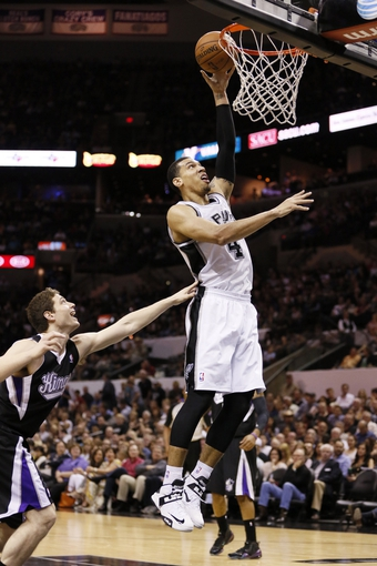 Apr 12, 2013; San Antonio, TX, USA; San Antonio Spurs guard Danny Green (4) drives to the basket past Sacramento Kings guard Jimmer Fredette (left) during the first half at the AT&T Center. Mandatory Credit: Soobum Im-USA TODAY Sports
