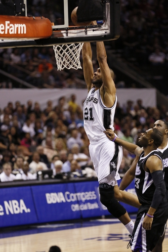 Apr 12, 2013; San Antonio, TX, USA; San Antonio Spurs forward Tim Duncan (21) dunks as Sacramento Kings guard Marcus Thornton (23) looks on during the first half at the AT&T Center. Mandatory Credit: Soobum Im-USA TODAY Sports