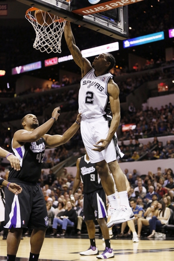 Apr 12, 2013; San Antonio, TX, USA; San Antonio Spurs forward Kawhi Leonard (2) dunks as Sacramento Kings forward Chuck Hayes (42) looks on during the first half at the AT&T Center. Mandatory Credit: Soobum Im-USA TODAY Sports