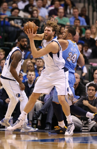 April 12, 2013; Dallas, TX, USA;  Dallas Mavericks forward Dirk Nowitzki (41) grabs a rebound during the second quarter against Denver Nuggets  center JaVale McGee (34) at the American Airlines Center. Mandatory Credit: Matthew Emmons-USA TODAY Sports