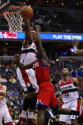 Apr 12, 2013; Washington, DC, USA; Washington Wizards power forward Kevin Seraphin (13) blocks the shot of Philadelphia 76ers point guard Jrue Holiday (11) in the fourth quarter at Verizon Center. The 76ers won 97-86. Mandatory Credit: Geoff Burke-USA TODAY Sports