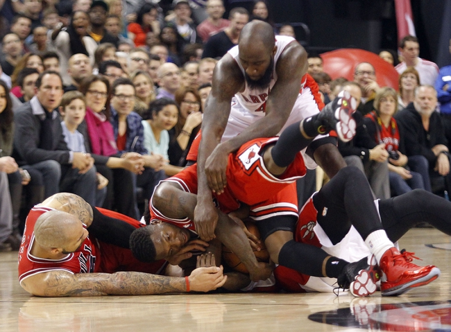 Apr 12, 2013; Toronto, Ontario, CAN; Toronto Raptors forward Quincy Acy (4) and Chicago Bulls forward Carlos Boozer (5) and guard Nate Robinson (2) battle for possession of the ball during the second half at the Air Canada Centre. Toronto defeated Chicago 97-88. Mandatory Credit: John E. Sokolowski-USA TODAY Sports