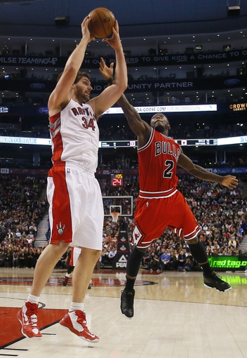 Apr 12, 2013; Toronto, Ontario, CAN;  Toronto Raptors center Aaron Gray (34) gets a rebound as Chicago Bulls guard Nate Robinson (2) defends at the Air Canada Centre. Toronto defeated Chicago 97-88. Mandatory Credit: John E. Sokolowski-USA TODAY Sports