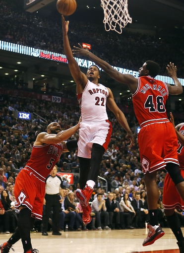 Apr 12, 2013; Toronto, Ontario, CAN; Toronto Raptors forward Rudy Gay (22) goes up to make a basket between Chicago Bulls forward Carlos Boozer (5) and center Nazr Mohammed (48) at the Air Canada Centre. Toronto defeated Chicago 97-88. Mandatory Credit: John E. Sokolowski-USA TODAY Sports