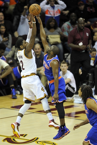 Apr 12, 2013; Cleveland, OH, USA; New York Knicks point guard Raymond Felton (2) defends a shot by Cleveland Cavaliers point guard Kyrie Irving (2) in the third quarter at Quicken Loans Arena. Mandatory Credit: David Richard-USA TODAY Sports