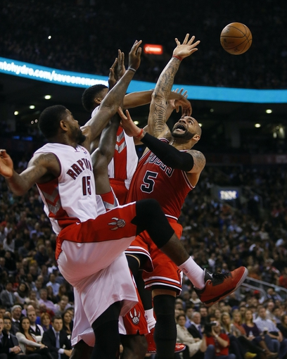 Apr 12, 2013; Toronto, Ontario, CAN; Toronto Raptors center-forward Amir Johnson (15) and Toronto Raptors forward Rudy Gay (22) defend against Chicago Bulls forward Carlos Boozer (5) at the Air Canada Centre. Toronto defeated Chicago 97-88. Mandatory Credit: John E. Sokolowski-USA TODAY Sports