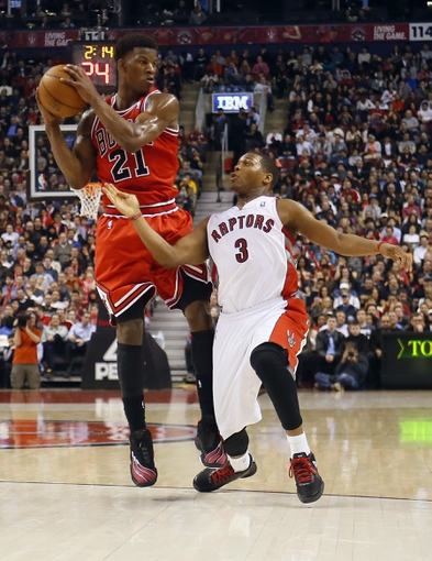 Apr 12, 2013; Toronto, Ontario, CAN; Chicago Bulls guard-forward Jimmy Butler (21) protects the ball against Toronto Raptors guard Kyle Lowry (3) at the Air Canada Centre. Toronto defeated Chicago 97-88. Mandatory Credit: John E. Sokolowski-USA TODAY Sports