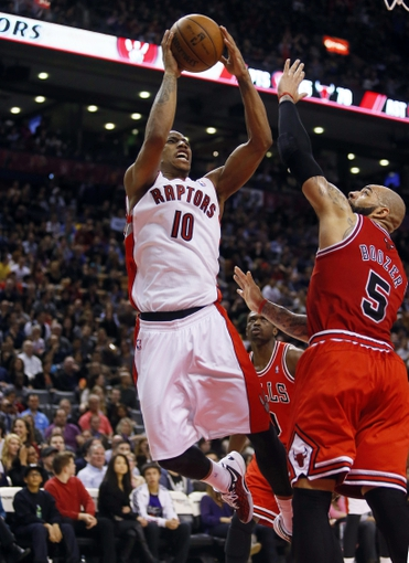 Apr 12, 2013; Toronto, Ontario, CAN; Toronto Raptors guard DeMar DeRozan (10) goes up to make a basket as Chicago Bulls forward Carlos Boozer (5) defends at the Air Canada Centre. Toronto defeated Chicago 97-88. Mandatory Credit: John E. Sokolowski-USA TODAY Sports